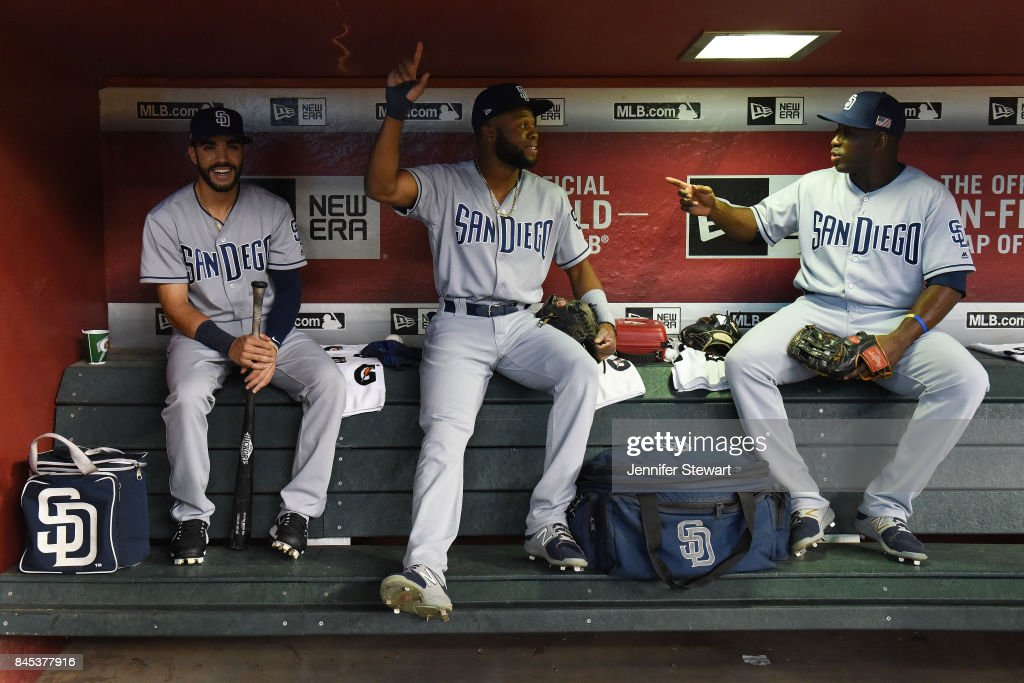 Carlos Asuaje #20, Manuel Margot #7 and Jose Pirela #2 of the San Diego Padres sit in the dugout prior to the MLB game against the Arizona Diamondbacks at Chase Field on September 10, 2017 in Phoenix, Arizona.