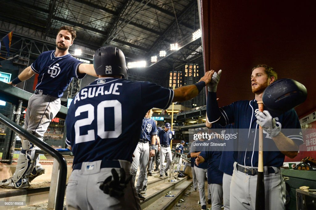 Carlos Asuaje #20 of the San Diego Padres is congratulated by Austin Hedges #18 and Cory Spangenberg #15 after scoring in the sixth inning of the MLB game against the Arizona Diamondbacks at Chase Field on July 5, 2018 in Phoenix, Arizona.