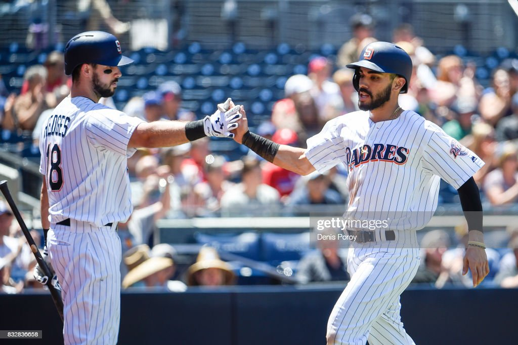 Carlos Asuaje #20 of the San Diego Padres, right, is congratulated by Austin Hedges #18 after scoring during the fourth inning of a baseball game against the Philadelphia Phillies at PETCO Park on August 16, 2017 in San Diego, California.