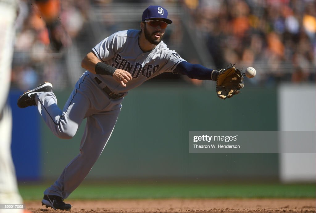 Carlos Asuaje #20 of the San Diego Padres throws to the ball to first base using his glove to throw out Brandon Crawford #35 of the San Francisco Giants in the bottom of the third inning at AT&T Park on September 30, 2017 in San Francisco, California.