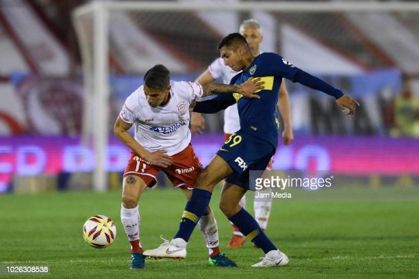 Carlos Auzqui of Huracan and Agustin Almendra of Boca Juniors fights for the ball during a match between Huracan and Boca Juniors as part of...