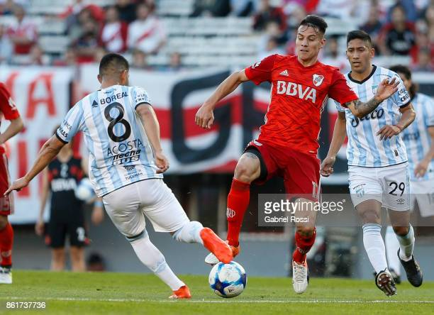 Carlos Auzqui of River Plate fights for the ball with Guillermo Acosta of Atletico de Tucuman during a match between River Plate and Atletico de...