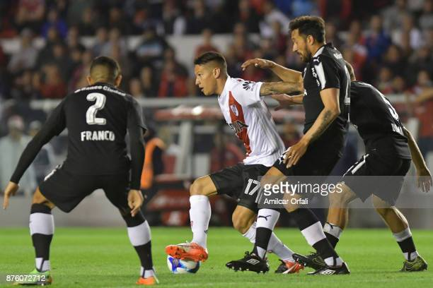 Carlos Auzqui of River Plate fights for the ball with Jonas Gutierrez and Alan Franco of Independiente during a match between Independiente and River...