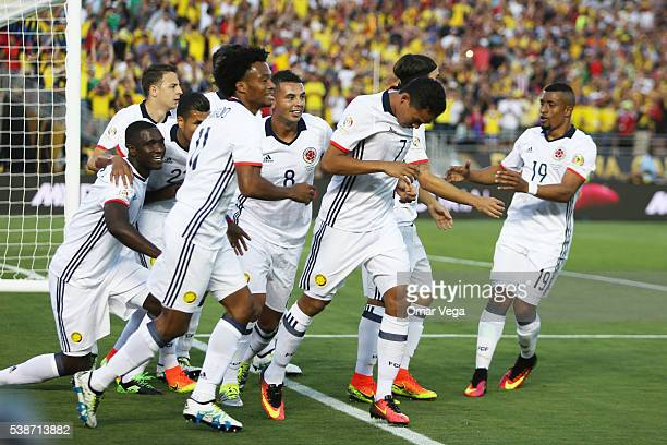 Carlos Bacca celebrates with teammates after scoring the first goal of his team during a group A match between Colombia and Paraguay at Rose Bowl...
