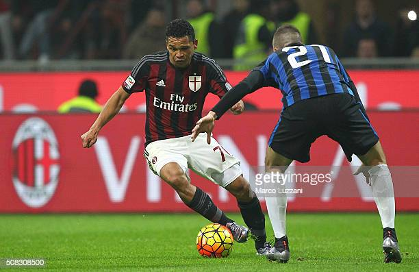 Carlos Bacca of AC Milan is challenged by Davide Santon of FC Internazionale Milano during the Serie A match between AC Milan and FC Internazionale...