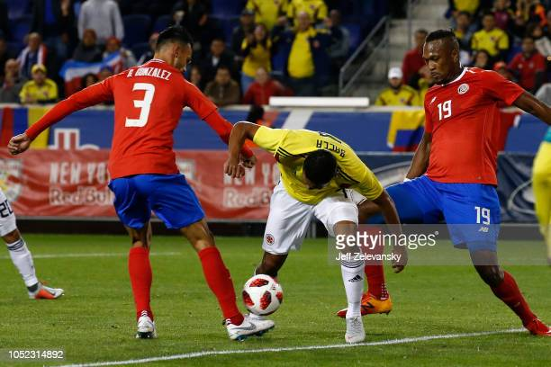 Carlos Bacca of Colombia drives between Giancarlo González of Costa Rica and Kendall Waston of Costa Rica during their match at Red Bull Arena on...