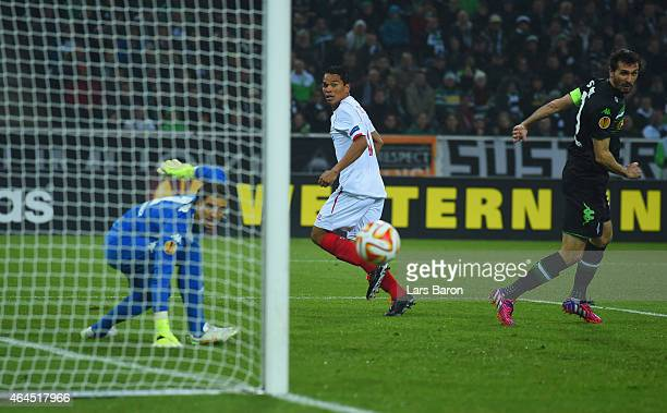 Carlos Bacca of Sevilla beats goalkeeper Yann Sommer of Borussia Moenchengladbach as Martin Stranzl of Borussia Moenchengladbach looks on to score...