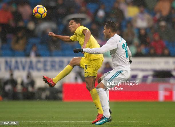 Carlos Bacca of Villarreal CF is challenged by Henrique Casemiro of Real Madrid during the La Liga match between Real Madrid and Villarreal at...