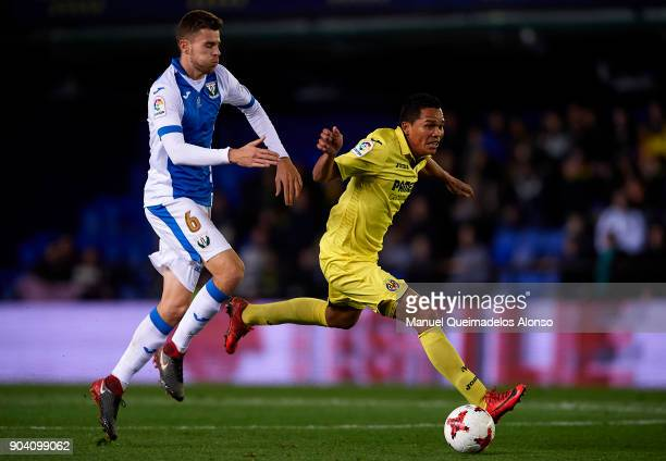 Carlos Bacca of Villarreal competes for the ball with Gerard Gumbau of Leganes during the Copa del Rey Round of 16 second Leg match between...