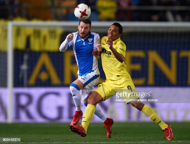 Carlos Bacca of Villarreal competes for the ball with Tito of Leganes during the Copa del Rey Round of 16 second Leg match between Villarreal CF and...