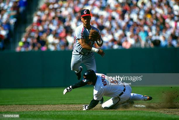 Carlos Baerga of the Cleveland Indians gets his throw off to first base while avoiding the slide of Cal Ripken Jr of the Baltimore Orioles during an...