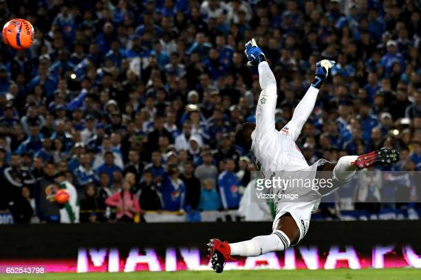 Carlos Bejarano goalkeeper of America fails to stop Elieser Quiñones of Millonarios from scoring the third goal of his team during a match between...