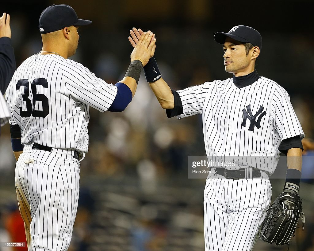 Carlos Beltran #36 and Ichiro Suzuki #31 of the New York Yankees high five each other after defeating the Detroit Tigers 5-1 in a MLB baseball game at Yankee Stadium on August 6, 2014 in the Bronx borough of New York City.