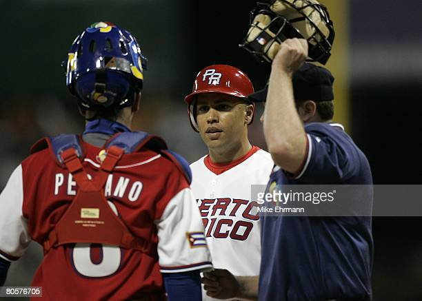 Carlos Beltran of team Puerto Rico argues with catcher Ariel Pestano about the position of the batboy during a 2nd round game against team Cuba...
