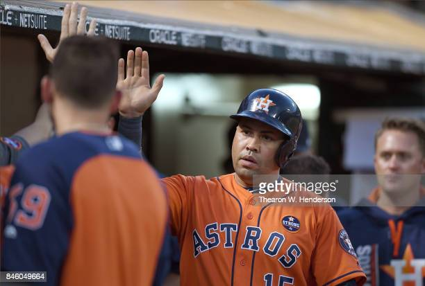 Carlos Beltran of the Houston Astros is congratulated by teammates after Beltran scored against the Oakland Athletics in the top of the seventh...