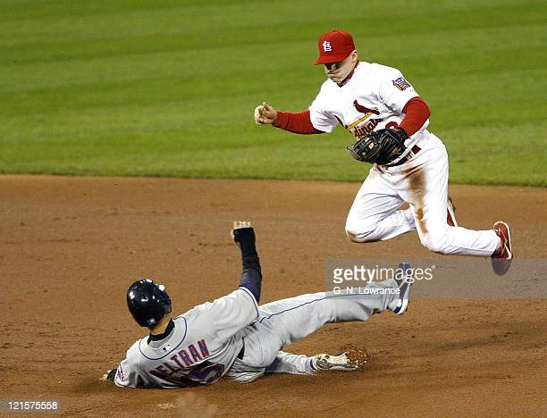 Carlos Beltran of the Mets is forced out at 2nd base as David Eckstein leaps in the air during game 5 action of the NLCS between the New York Mets...