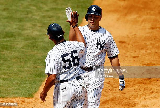 Carlos Beltran of the New York Yankees celebrates his sixth inning RBI base hit against the Seattle Mariners with first base coach Tony Pena at...