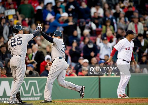 Carlos Beltran of the New York Yankees is congratulated by Mark Tiexeira after scoring a run against Felix Doubront of the Boston Red Sox in the...