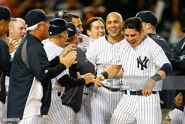 Carlos Beltran of the New York Yankees is mobbed by his teammates after hitting a game-winning walk-off three run home run in the ninth inning...