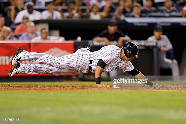 Carlos Beltran of the New York Yankees leaps back to touch home plate to score a run in the fourth inning against the Cleveland Indians on August 21...