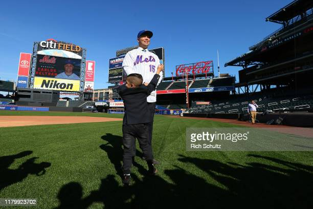 Carlos Beltran poses for pictures as his son Evan Carlos approaches after being introduced as the next manager of the New York Mets during a press...