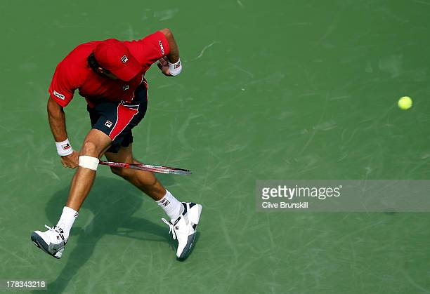 Carlos Berlocq of Argentina returns a shot through his legs during his men's singles second round match against Roger Federer of Switzerland on Day...