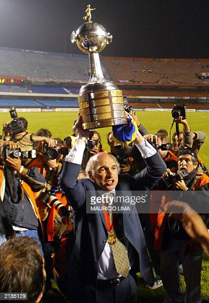 Carlos Bianchi coach of Argentina's Boca Juniors holds up the trophy after his team won the match against Brazil's Santos in their Libertadores Cup...
