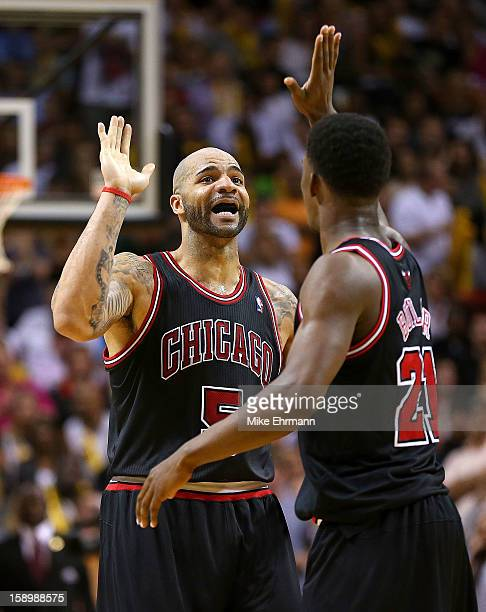 Carlos Boozer and Jimmy Butler of the Chicago Bulls celebrate during a game against the Miami Heat at AmericanAirlines Arena on January 4 2013 in...