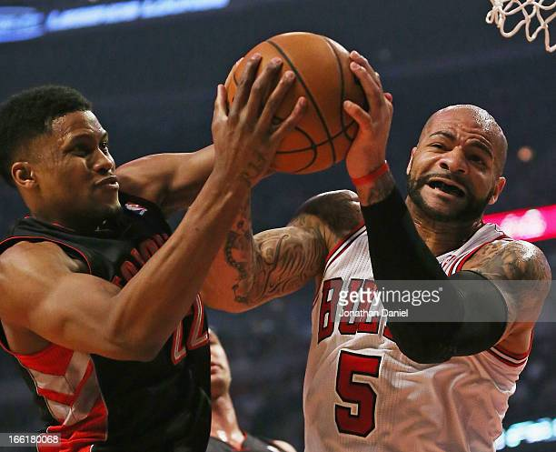 Carlos Boozer of the Chicago Bulls battles for a rebound with Rudy Gay of the Toronto Raptors at the United Center on April 9 2013 in Chicago...