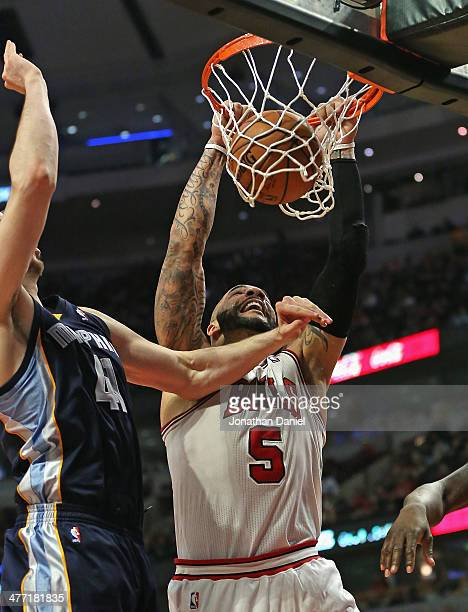 Carlos Boozer of the Chicago Bulls dunks against Kosta Koufos of the Memphis Grizzlies at the United Center on March 7 2014 in Chicago Illinois The...