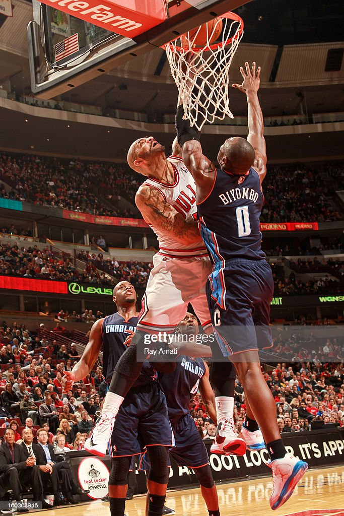 Carlos Boozer #5 of the Chicago Bulls dunks against Ramon Sessions #7 of the Charlotte Bobcats on January 28, 2013 at the United Center in Chicago, Illinois.