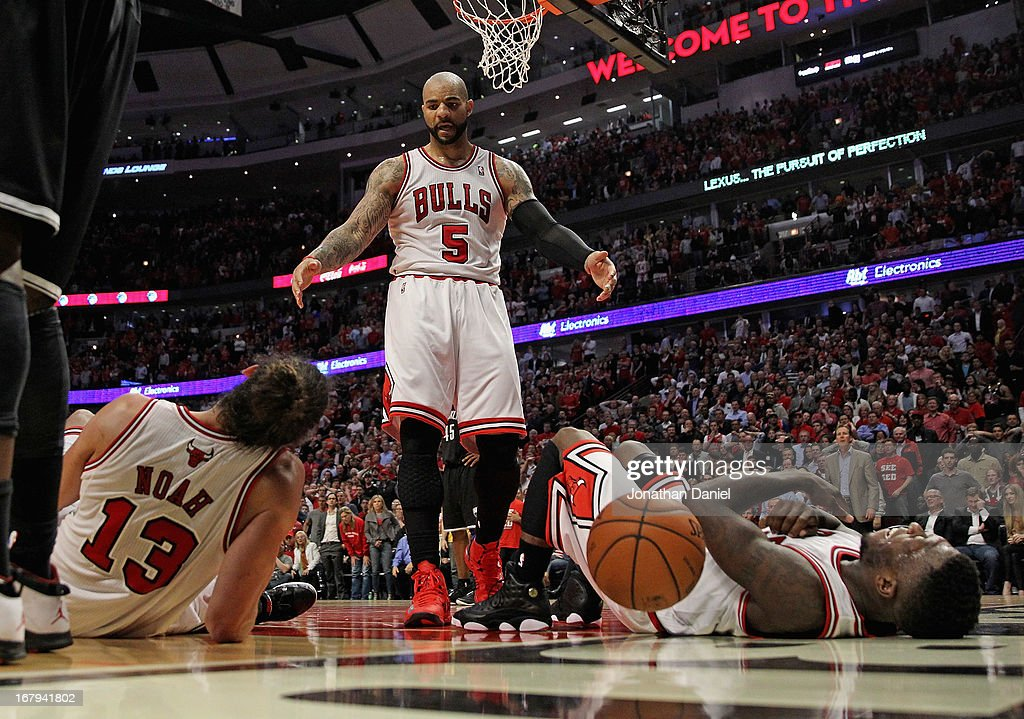 Carlos Boozer #5 of the Chicago Bulls moves to help up teammates Joakim Noah #13 (L) and Nate Robinson #2 after a play against the Brooklyn Nets in Game Six of the Eastern Conference Quarterfinals during the 2013 NBA Playoffs at the United Center on May 2, 2013 in Chicago, Illinois. The Nets defeated the Bulls 95-92.