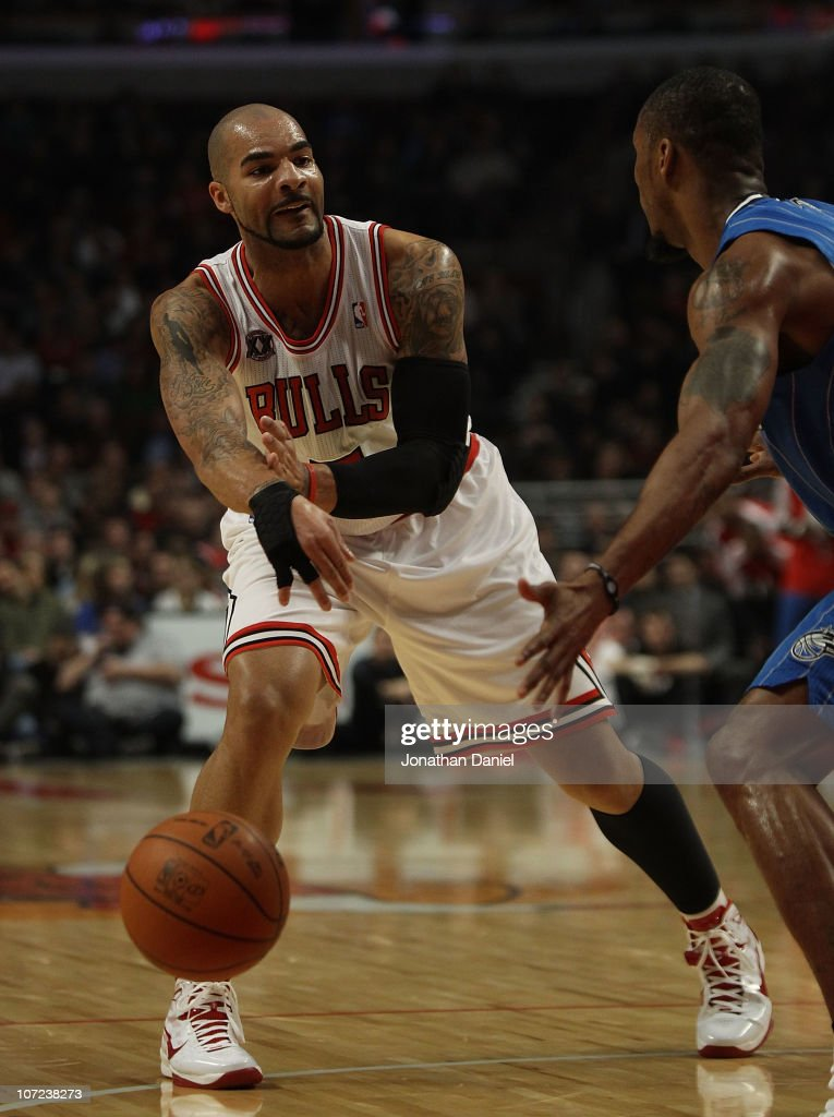 Carlos Boozer #5 of the Chicago Bulls passes the ball around Rashard Lewis #9 of the Orlando Magic in his first start of the season at the United Center on December 1, 2010 in Chicago, Illinois.