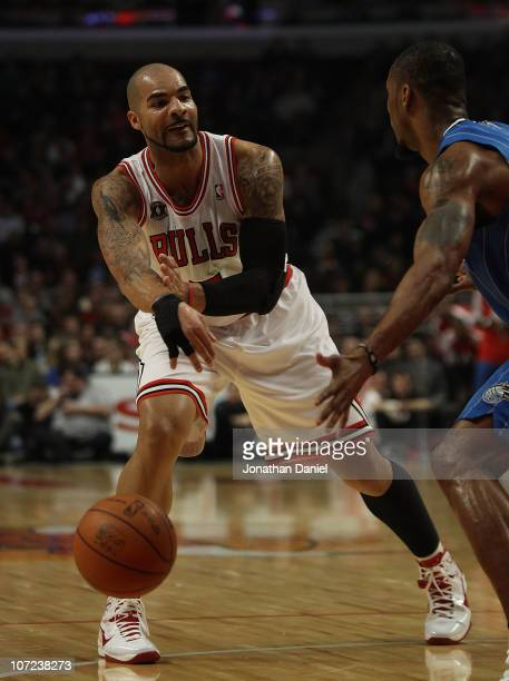 Carlos Boozer of the Chicago Bulls passes the ball around Rashard Lewis of the Orlando Magic in his first start of the season at the United Center on...
