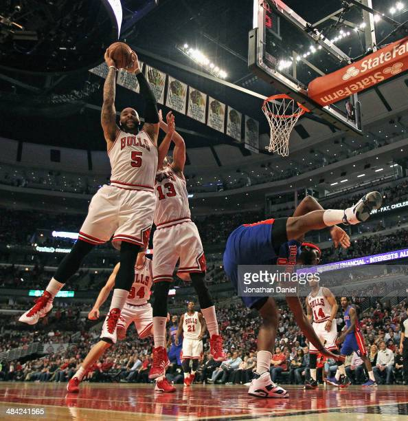 Carlos Boozer of the Chicago Bulls rebounds over teammate Joakim Noah as Andre Drummond of the Detroit Pistons looses his balance at the United...