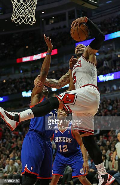 Carlos Boozer of the Chicago Bulls rebounds over Thaddeus Young of the Phildelphia 76ers at the United Center on February 28 2013 in Chicago Illinois...