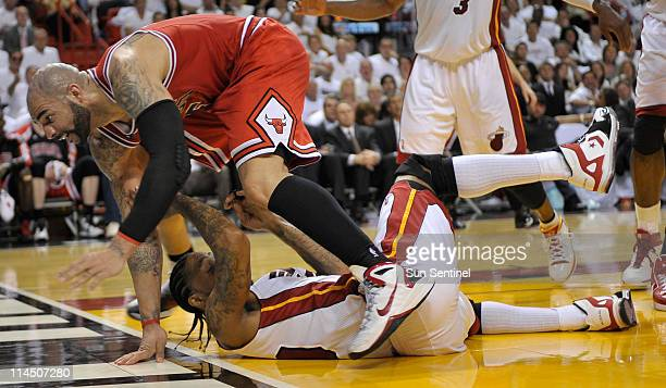 Carlos Boozer of the Chicago Bulls runs over Udonis Haslem of the Miami Heat in the second quarter during Game 3 of the NBA Eastern Conference Finals...
