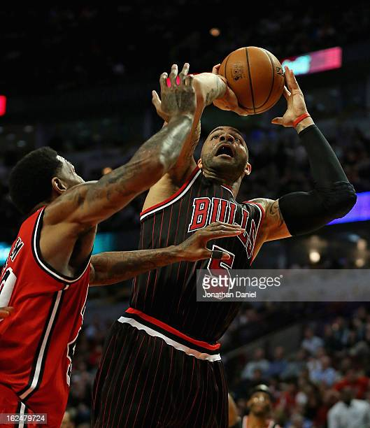 Carlos Boozer of the Chicago Bulls shoots against Udonis Haslem of the Miami Heat at the United Center on February 21 2013 in Chicago Illinois The...