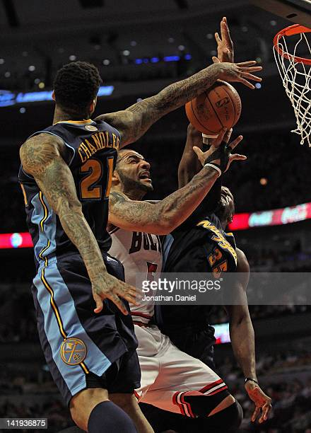 Carlos Boozer of the Chicago Bulls tries to get off a shot between Wilson Chandler and Kenneth Faried of the Denver Nuggets at the United Center on...