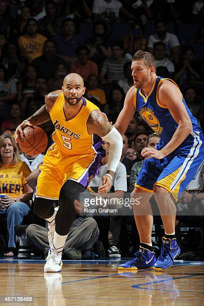 Carlos Boozer of the Los Angeles Lakers handles the ball against David Lee of the Golden State Warriors on October 12 2014 at Citizens Business Bank...