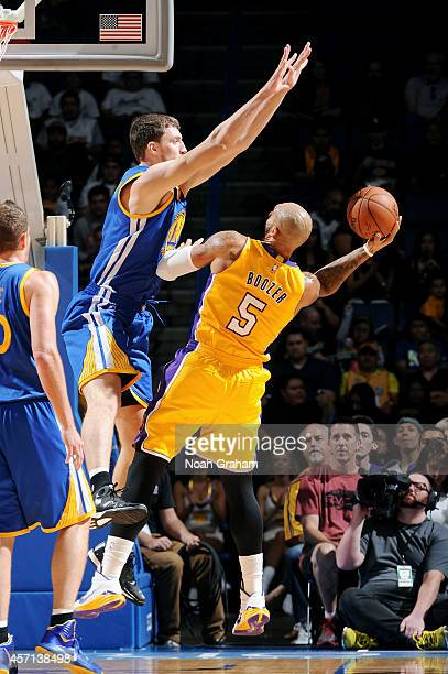 Carlos Boozer of the Los Angeles Lakers shoots the ball against Andrew Bogut of the Golden State Warriors on October 12 2014 at Citizens Business...