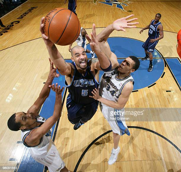 Carlos Boozer of the Utah Jazz shoots against JaVale McGee and Shaun Livingston of the Washington Wizards at the Verizon Center on March 27 2010 in...