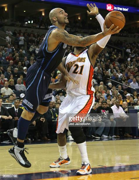 Carlos Boozer of the Utah Jazz shoots against Ronny Turiaf of the Golden State Warriors during an NBA game at Oracle Arena at Oracle Arena on...