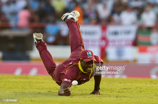 Carlos Brathwaite of the West Indies attempts to catch Alex Hales of England during a T20 match between the West Indies and England at Darren Sammy...