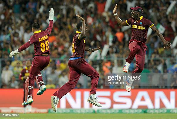 Carlos Brathwaite of the West Indies celebrates the wicket of Joe Root of England with teammate Darren Sammy, Captain of the West Indies and Denesh...