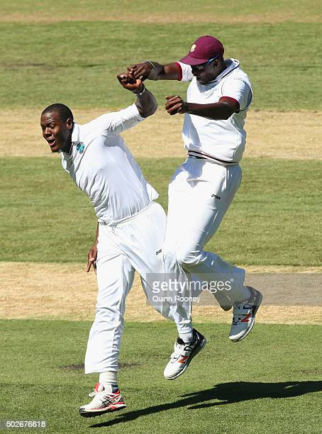 Carlos Brathwaite of the West Indies is congratulated by Jason Holder after getting the wicket of David Warner of Australia during day three of the...