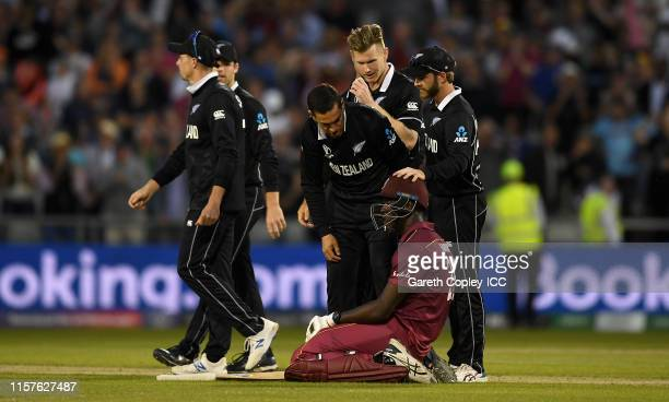 Carlos Brathwaite of the West Indies is consoled New Zealand fielders Ross Taylor and Kane Williamson after losing the Group Stage match of the ICC...