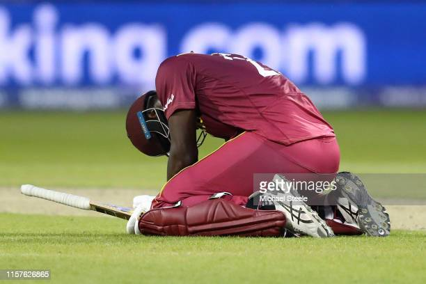 Carlos Brathwaite of West Indies sinks to his knees after being caught by Trent Boult off the bowling of Jimmy Neesham for 101 runs and losing by 5...