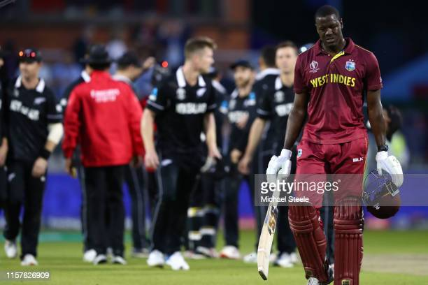Carlos Brathwaite of West Indies walks off dejectedly after being caught by Trent Boult off the bowling of Jimmy Neesham for 101 runs and losing by 5...
