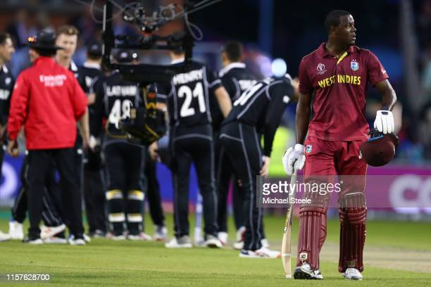Carlos Brathwaite of West Indies walks off dejectedly after being last man out for 101 runs and losing by 5 runs during the Group Stage match of the...